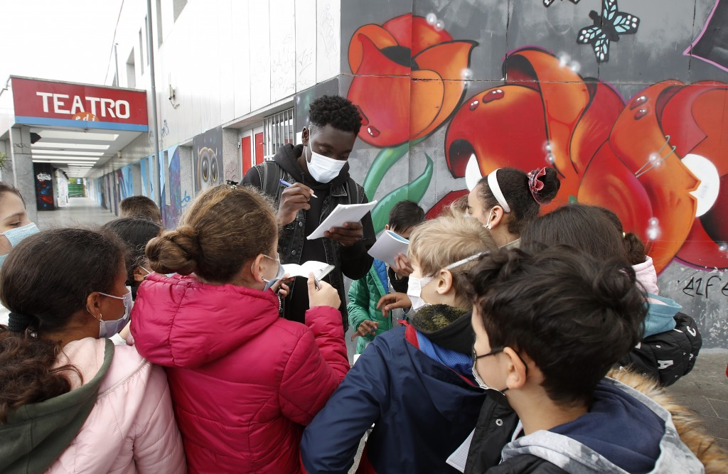 """Actor Giuseppe Dave Seke signs autographs to children, in Milan, Italy, Tuesday, April 27, 2021. The Netflix series """"Zero,"""" which premiered globally l..."""