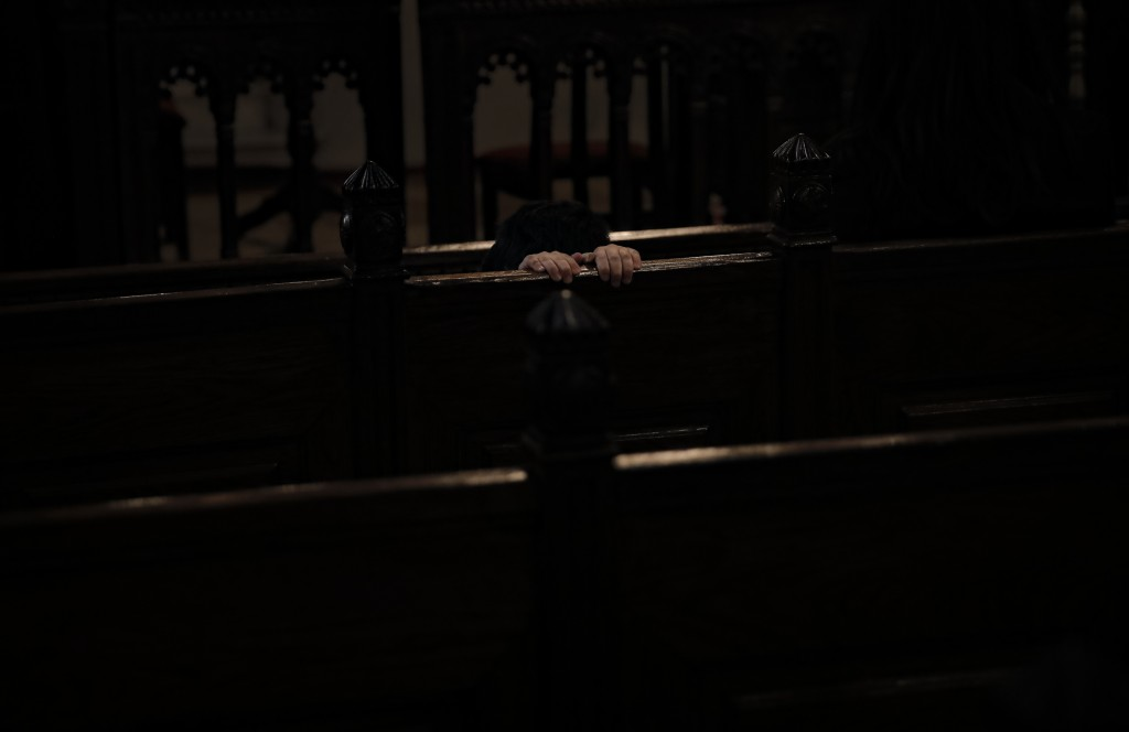 A boy from the Armenian community in Romania holds on to a bench during a Maundy Thursday religious service, at the Armenian Church in Bucharest, Roma...