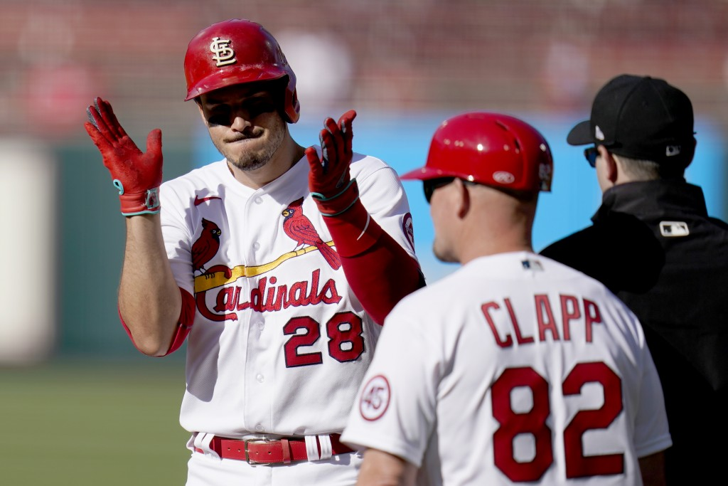 St. Louis Cardinals' Nolan Arenado (28) celebrates after hitting an RBI single as Cardinals first base coach Stubby Clapp (82) stands nearby during th...