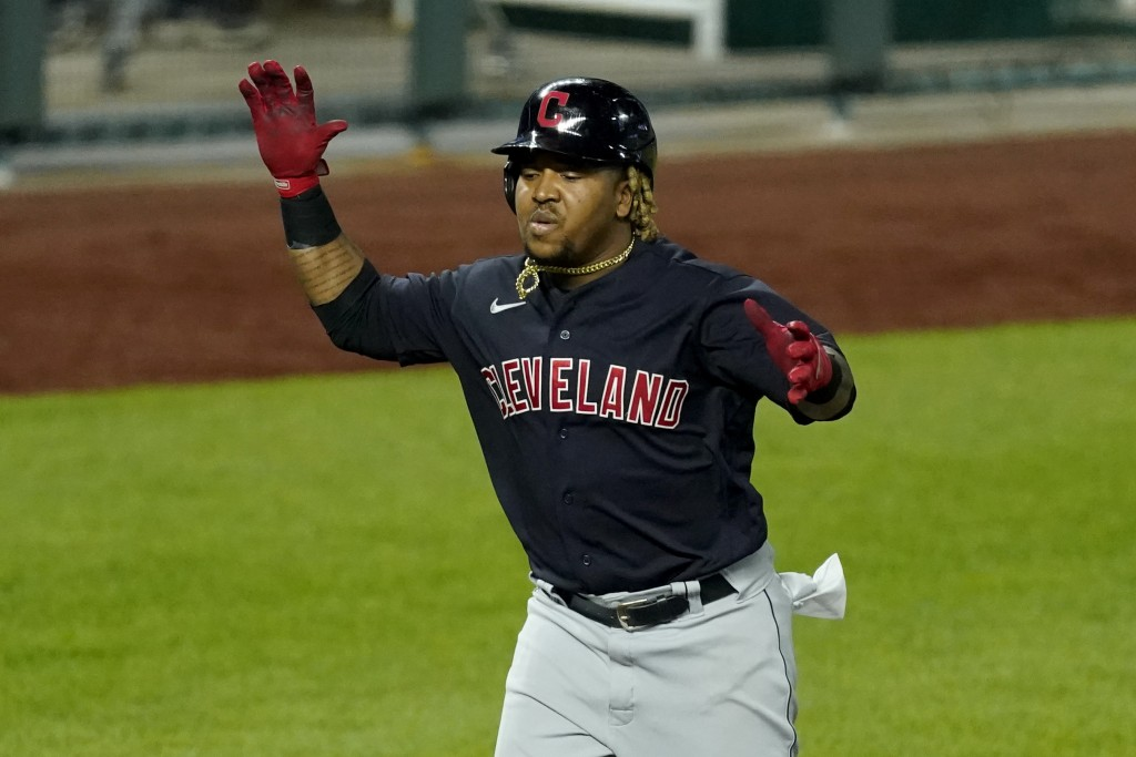Cleveland Indians' Jose Ramirez celebrates as he runs home after hitting a solo home run during the eighth inning of a baseball game against the Kansa...