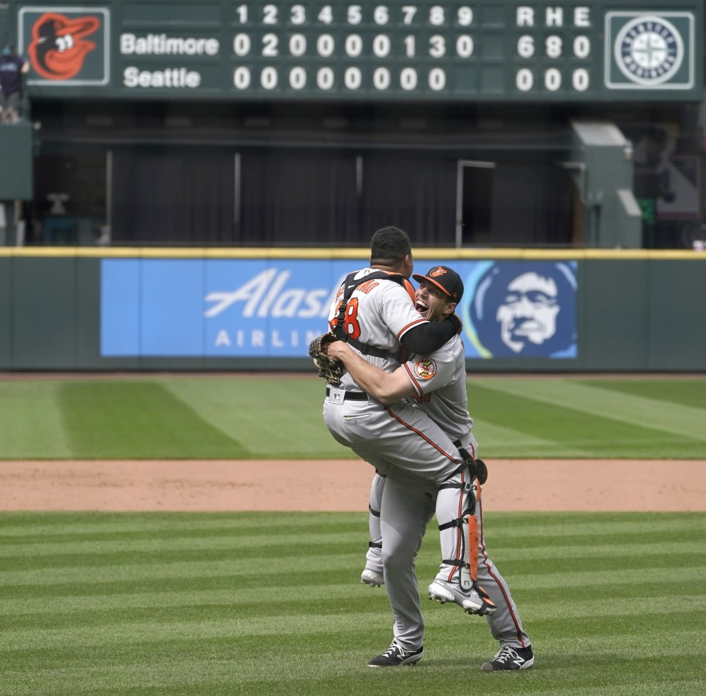 Baltimore Orioles starting pitcher John Means, right, hugs catcher Pedro Severino after Means threw a no-hitter baseball game against the Seattle Mari...