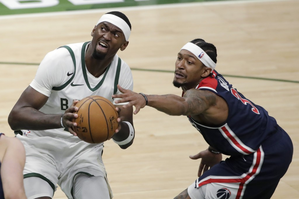 Washington Wizards' Bradley Beal, right, reaches for the ball as Milwaukee Bucks' Bobby Portis drives to the basket during the second half of an NBA b...
