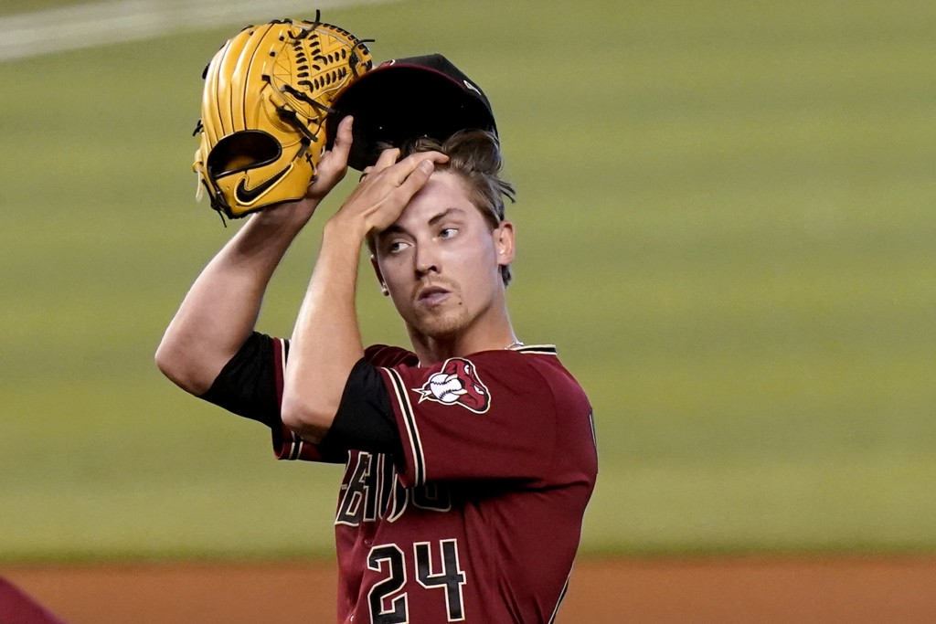 Arizona Diamondbacks starting pitcher Luke Weaver (24) adjusts this cap after the Miami Marlins scored two runs during the first inning of a baseball ...