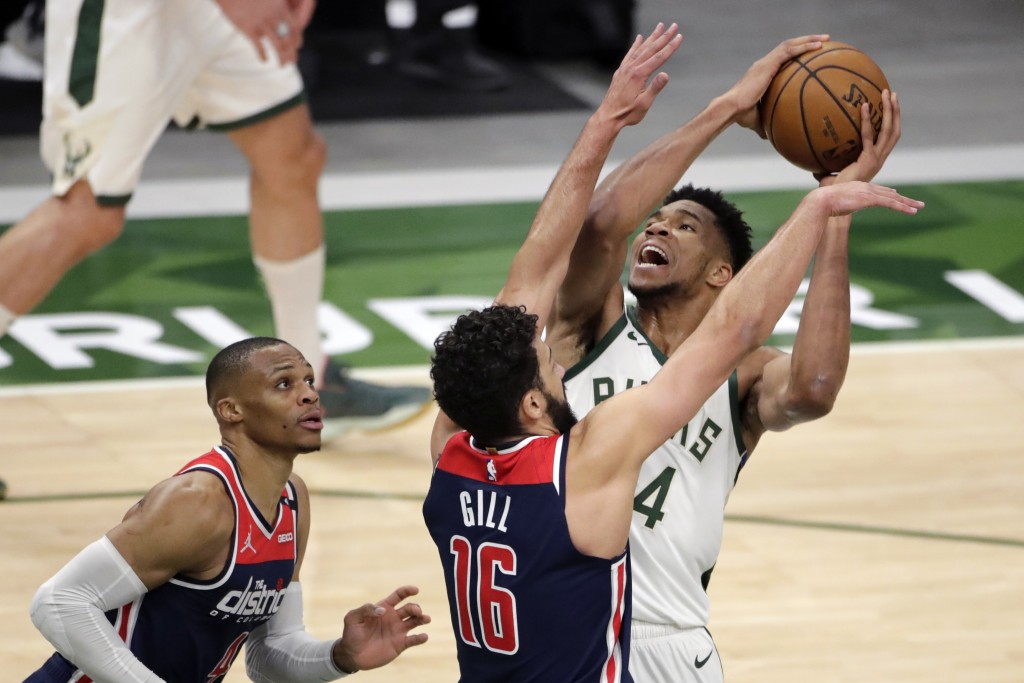 Milwaukee Bucks' Giannis Antetokounmpo drives to the basket against Washington Wizards' Anthony Gill and Russell Westbrook during the second half of a...