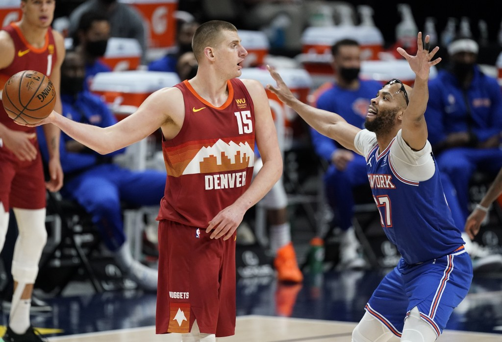 Denver Nuggets center Nikola Jokic (15) looks to pass the ball as New York Knicks center Taj Gibson defends in the second half of an NBA basketball ga...