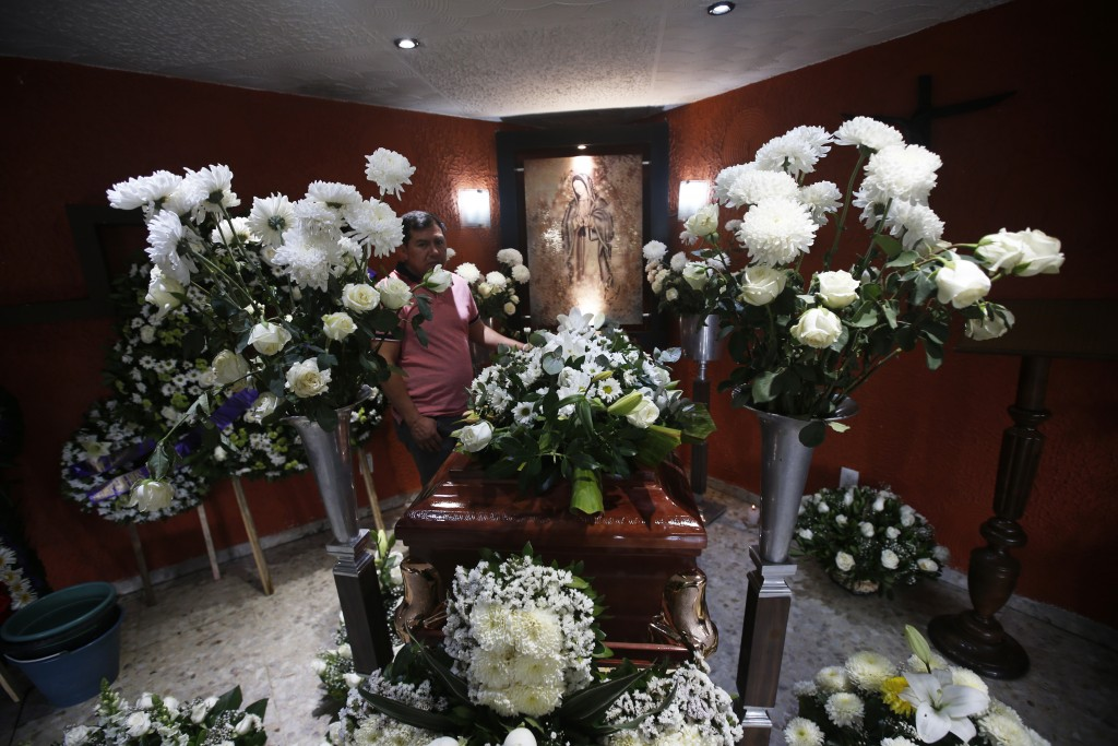 Funeral flowers surround the casket containing the remains of 37-year-old Liliana Lopez who died in the Mexico City Metro collapse disaster, during a ...