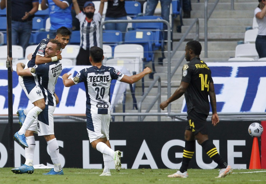 Maximiliano Meza of Mexico's Monterrey, left, is congratulated by his teammates after scoring his team's second goal against Unites States' Columbus C...