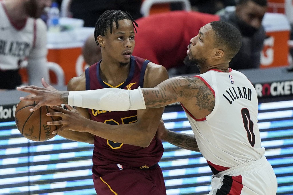 Portland Trail Blazers' Damian Lillard (0) defends against Cleveland Cavaliers' Isaac Okoro during the second half of an NBA basketball game Wednesday...