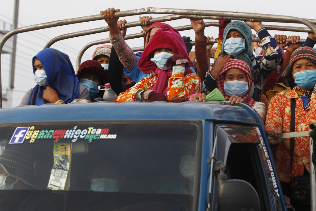 Garment workers stand on a truck as they head to work outside Phnom Penh, Cambodia, Thursday, May 6, 2021. Cambodia on Thursday ended a lockdown in th...
