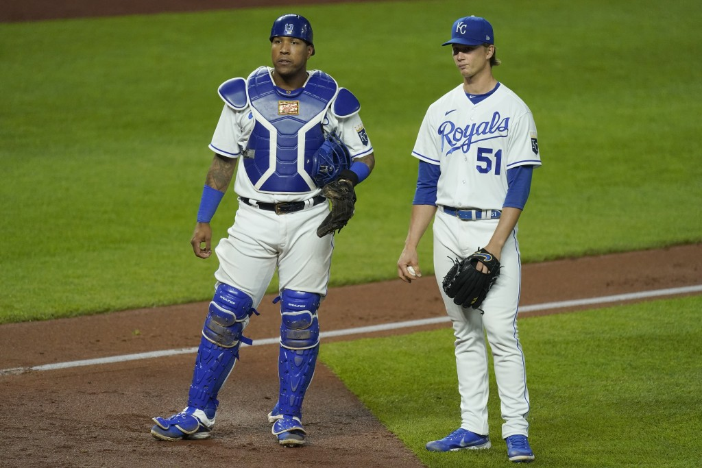 Kansas City Royals starting pitcher Brady Singer and catcher Salvador Perez wait while a play is reviewed during the sixth inning of a baseball game a...