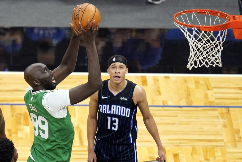 Boston Celtics center Tacko Fall (99) makes a shot in front of Orlando Magic guard R.J. Hampton (13) during the second half of an NBA basketball game,...