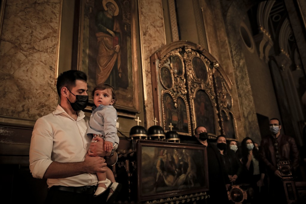 A man of the Armenian community in Romania holds a young child during the Easter religious service, at the Armenian Church in Bucharest, Romania, Satu...