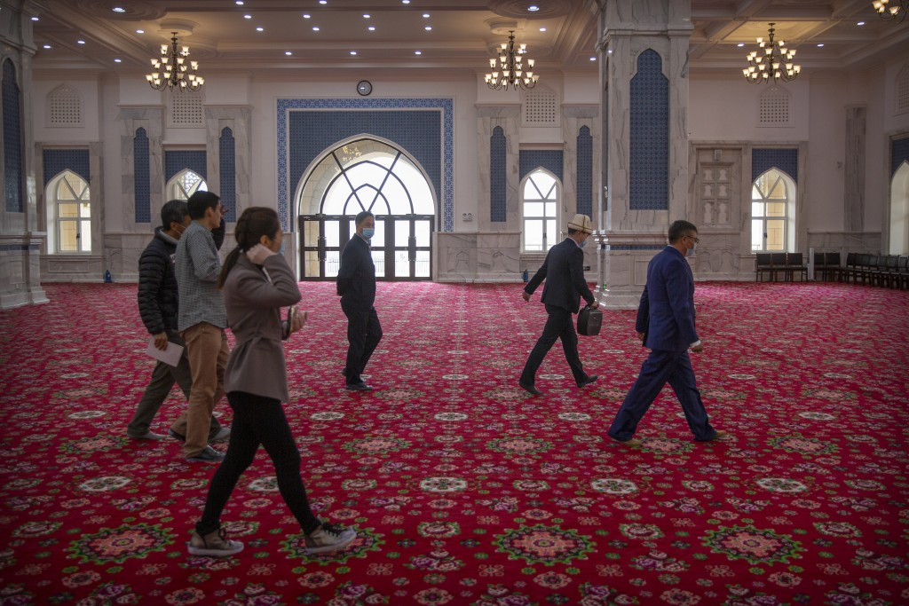 Abit Qazbay, right, an instructor at the Xinjiang Islamic Institute, and government officials walk through the prayer hall during a government organiz...