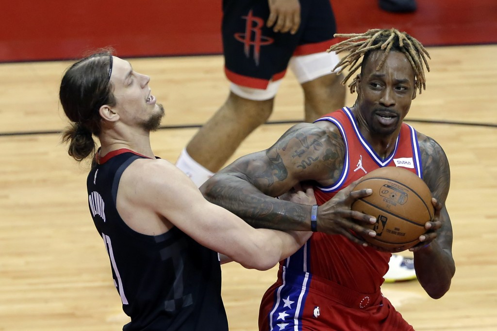 Houston Rockets forward Kelly Olynyk, left, takes an elbow from Philadelphia 76ers center Dwight Howard, right, as he looks for a shot during the firs...