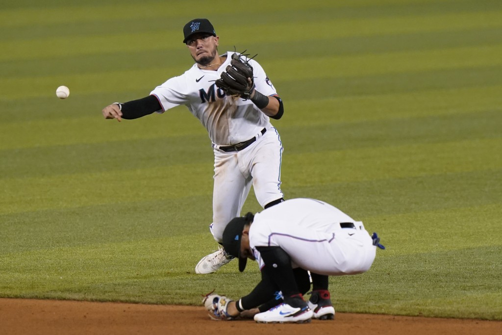 Miami Marlins shortstop Miguel Rojas throws to first where Arizona Diamondbacks' Pavin Smith was out during the seventh inning of a baseball game, Wed...