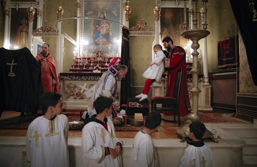 Iraq-born Archbishop Datev Hagopian, left, prepares to symbolically wash the feet of a boy during a Maundy Thursday religious service, at the Armenian...