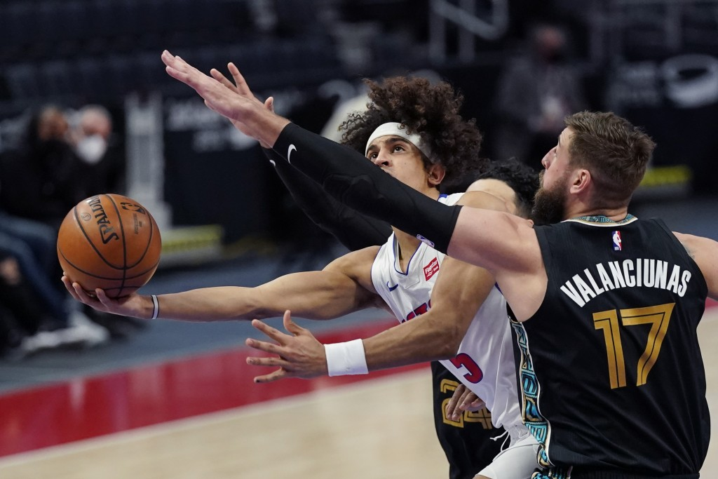 Detroit Pistons guard Frank Jackson (5) attempts a layup as Memphis Grizzlies center Jonas Valanciunas (17) defends during the first half of an NBA ba...