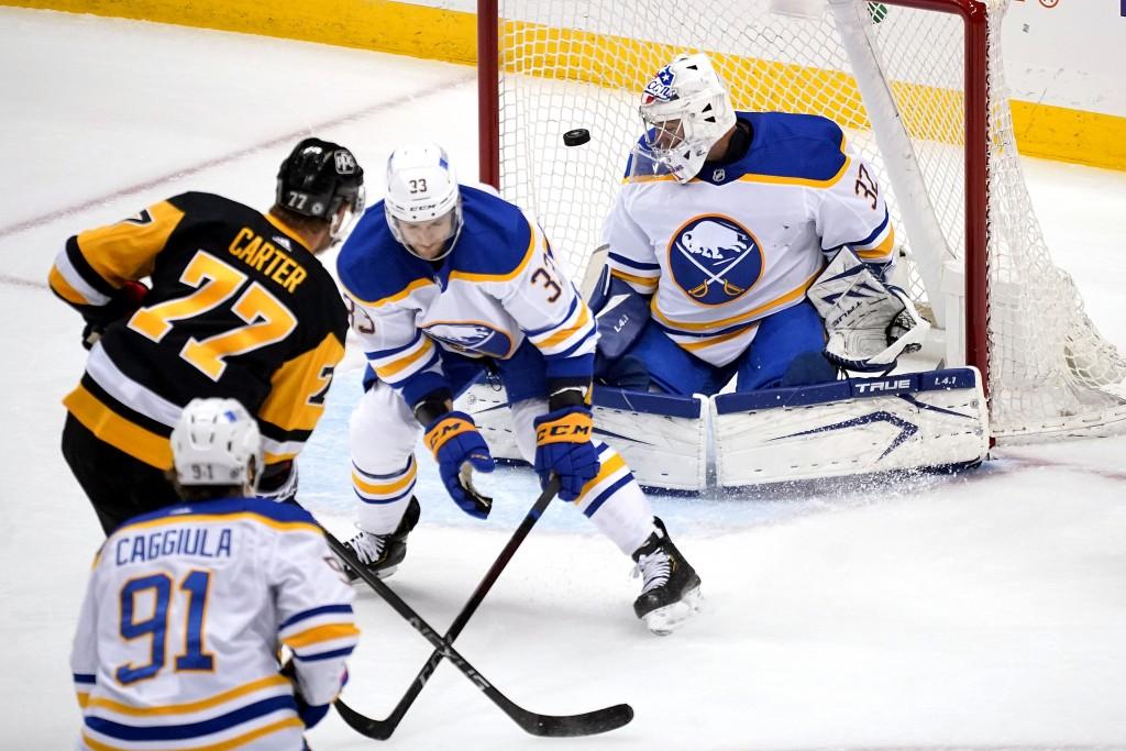 Pittsburgh Penguins center Jeff Carter (77) pust a shot past Buffalo Sabres goaltender Michael Houser (32) with Sabres' Colin Miller (33) defending du...