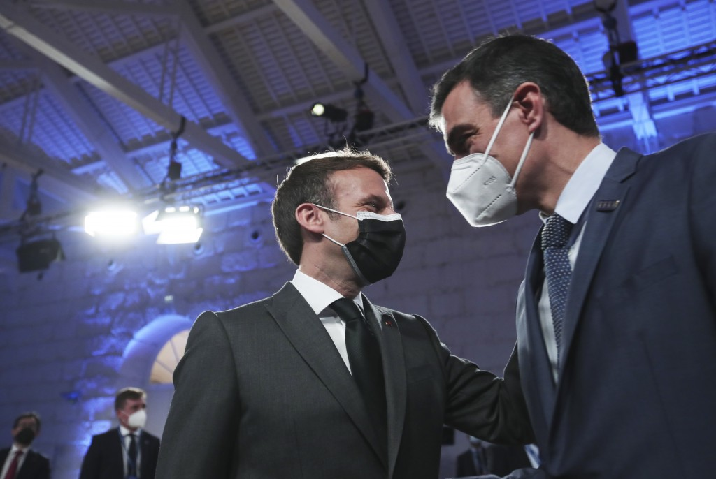 French President Emmanuel Macron, left, speaks with Spain's Prime Minister Pedro Sanchez during the opening ceremony of an EU summit at the Alfandega ...