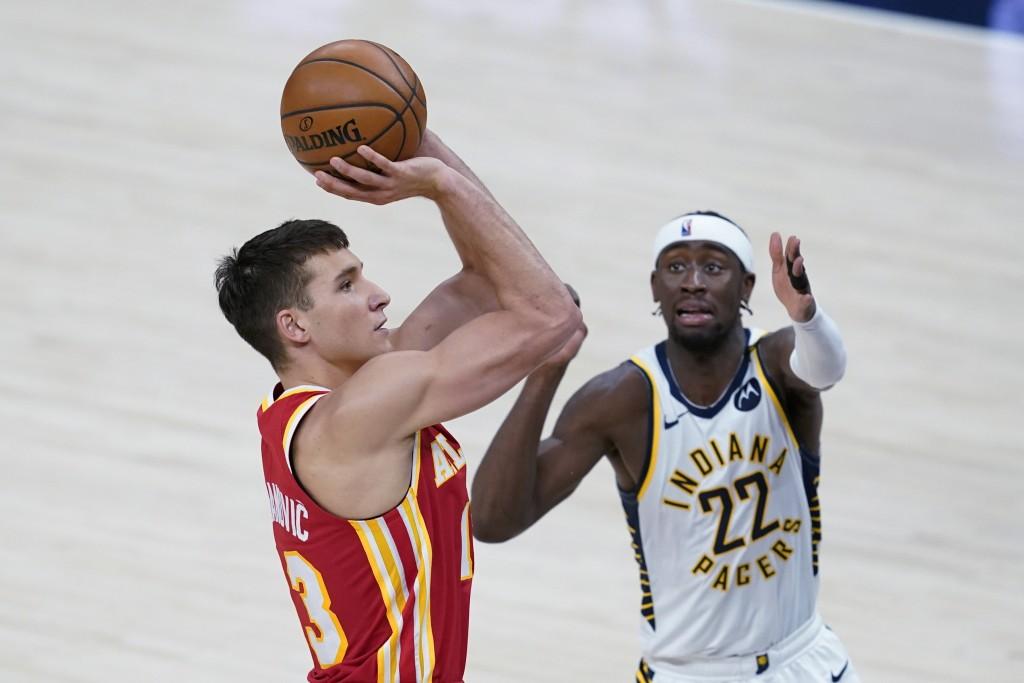 Atlanta Hawks' Bogdan Bogdanovic (13) shoots next to Indiana Pacers' Caris LeVert (22) during the first half of an NBA basketball game Thursday, May 6...
