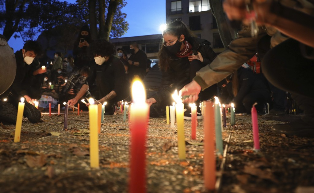 People light candles in a vigil to honor those that died during anti-government protests, in Bogota, Colombia, Thursday, May 6, 2021. The protests tha...
