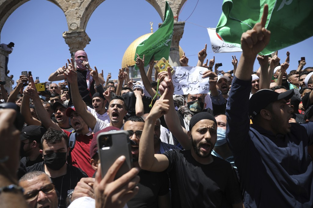 Worshippers chant slogans and wave Hamas flags during a protest against the likely evictions of Palestinian families from the homes, after the last Fr...