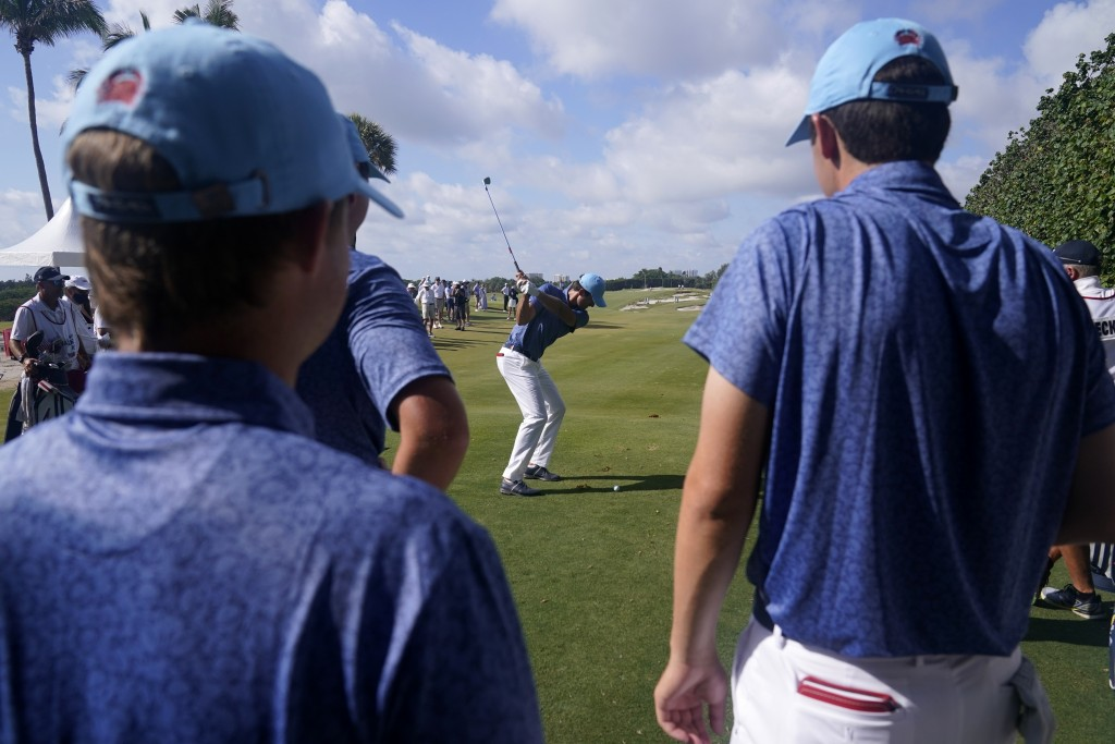 Members of the USA team watch as Stewart Hagestad tees off during a practice day for the Walker Cup golf tournament at Seminole Golf Club in Juno Beac...