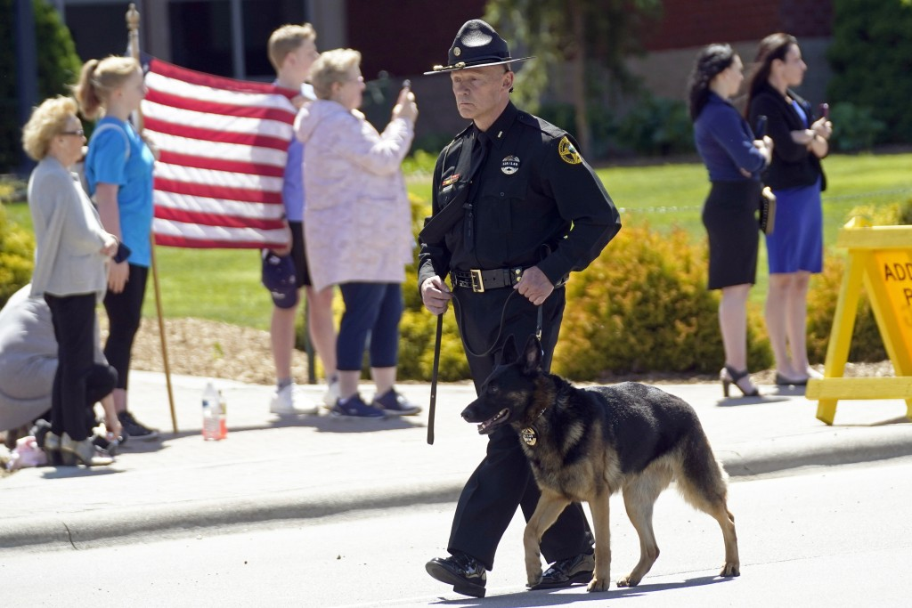 A K-9 officer leads a processional to the Holmes Convocational Center for the funeral services of Watauga County Sheriff's Deputies Sgt. Chris Ward an...