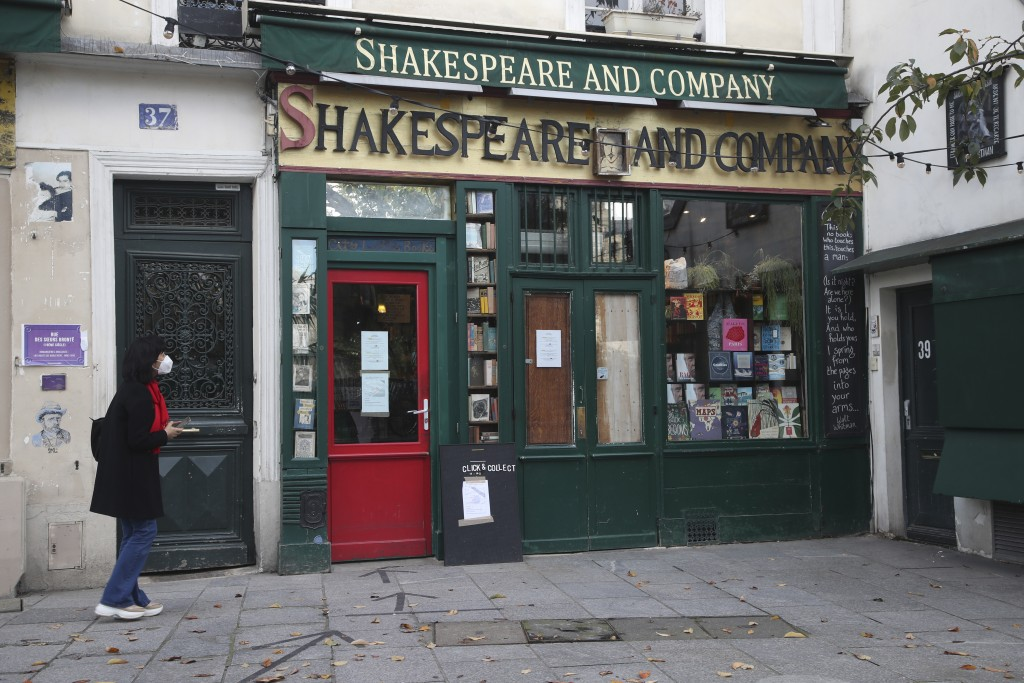 FILE - In this Tuesday, Nov. 3, 2020 file photo, a woman walks by the closed English and American literature Shakespeare bookstore in Paris. European ...