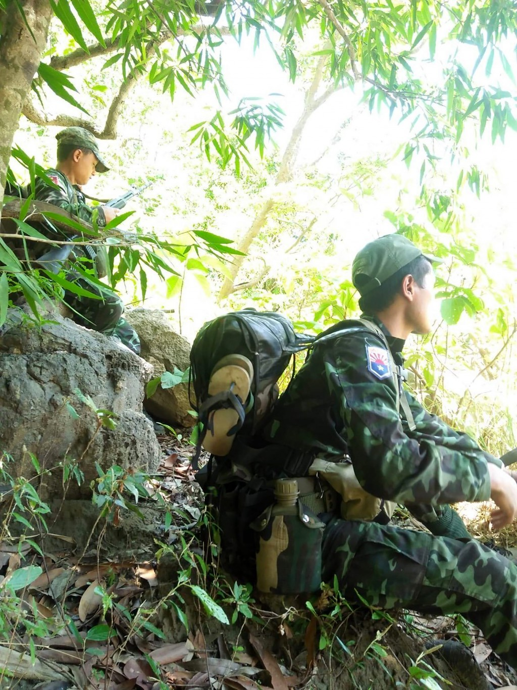 In this photo provided by Karen National Liberation Army, soldiers of the Karen National Liberation Army are seated in a forest Friday, May 7, 2021, i...