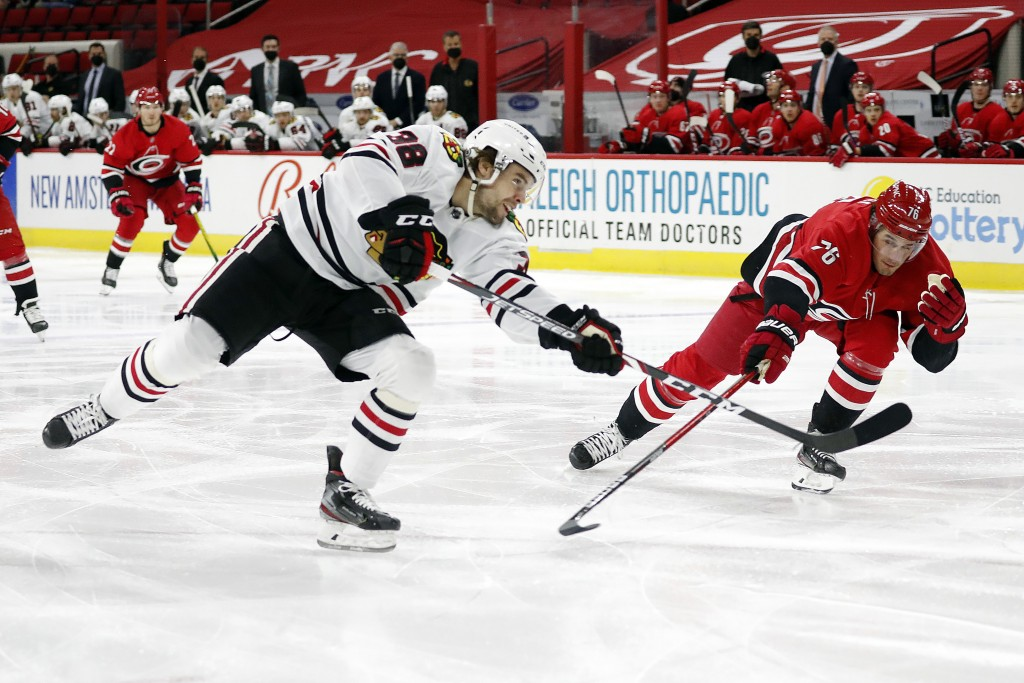 Chicago Blackhawks' Alex DeBrincat (12) shoots the puck past Carolina Hurricanes' Brady Skjei (76) during the first period of an NHL hockey game in Ra...