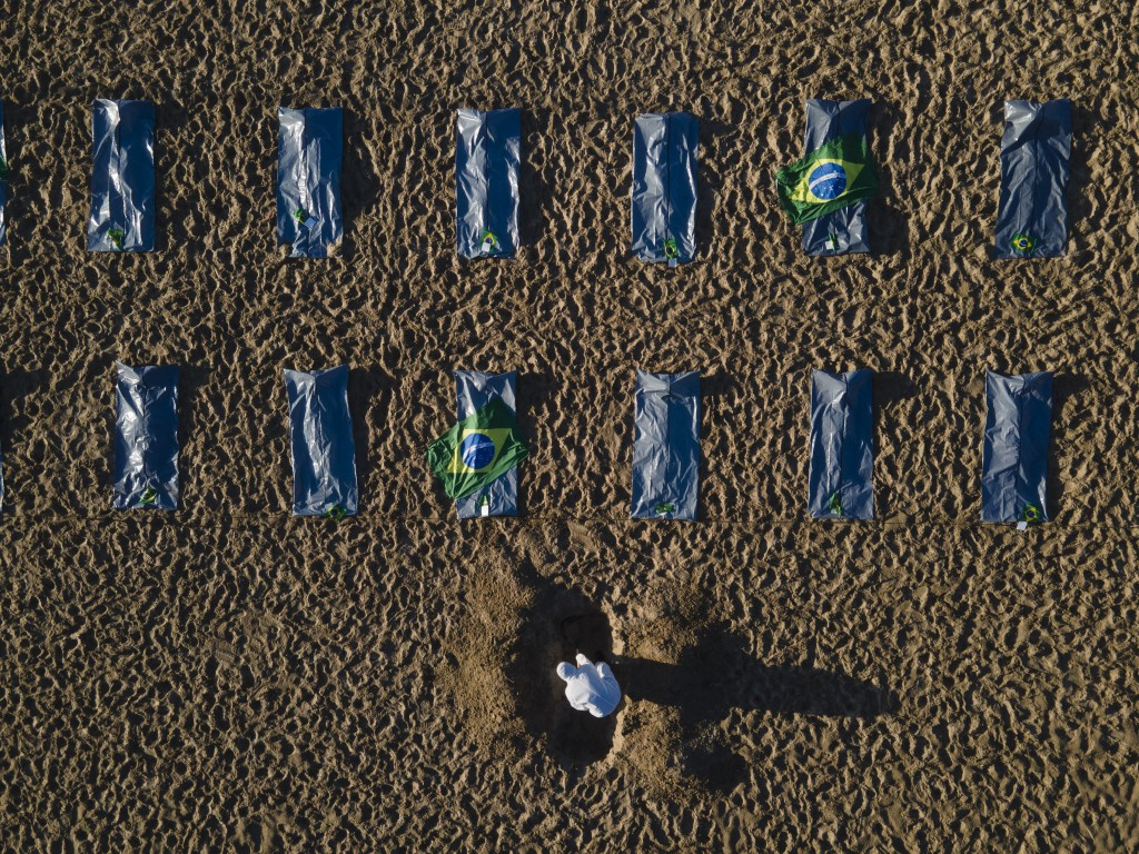 """An activist from the NGO """"Rio de Paz"""" digs a mock grave in the sand by symbolic body bags on Copacabana beach to protest the government's handling of ..."""