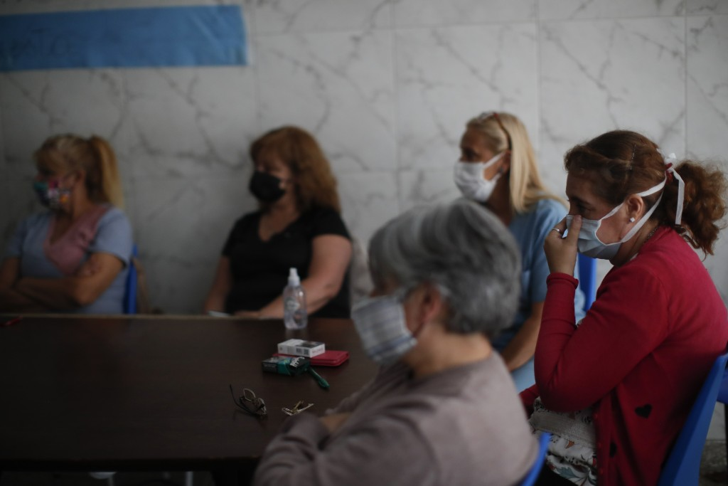 Former workers sit inside San Andres Clinic which they have been occupying since it closed at the start of the year following the death of the hospita...