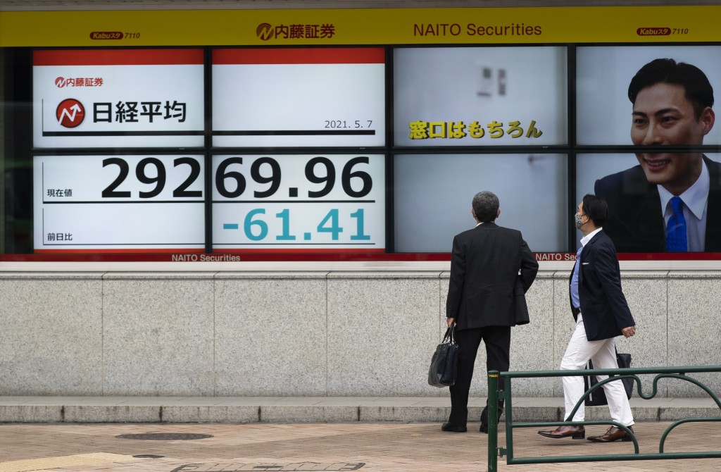 Men look at monitors showing Japan's Nikkei 225 index at a securities firm in Tokyo on Friday, May 7, 2021. Asian shares rose Friday on optimism about...