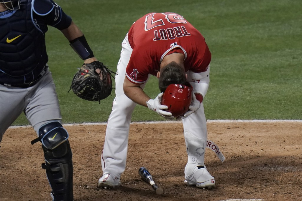 Los Angeles Angels' Mike Trout removes his helmet after striking out during the eighth inning of the team's baseball game against the Tampa Bay Rays, ...