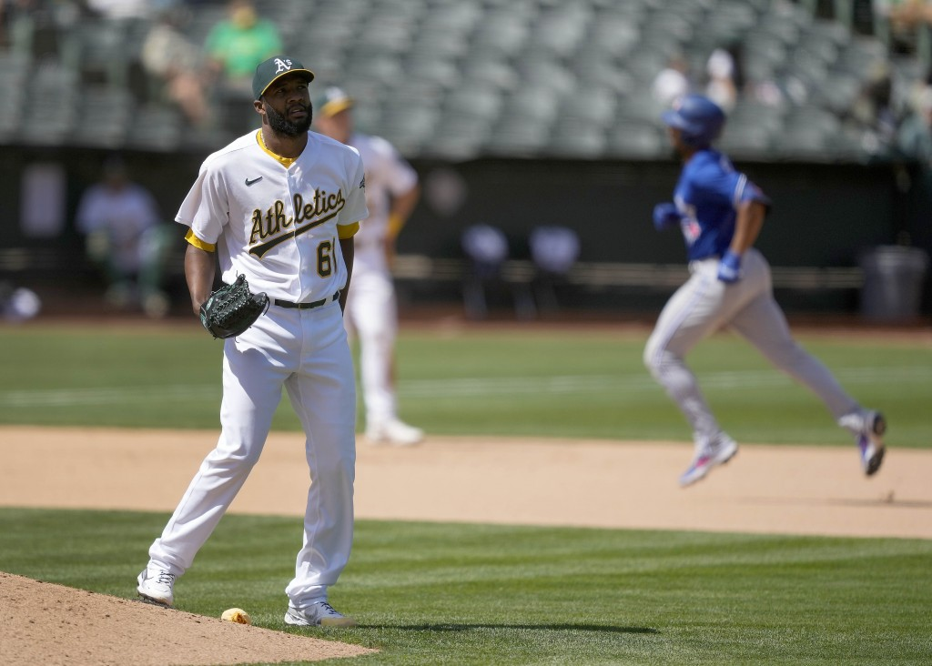 Oakland Athletics relief pitcher Reymin Guduan (61) stands on the edge of the mound as Toronto Blue Jays' Marcus Semien, right, runs the bases after h...