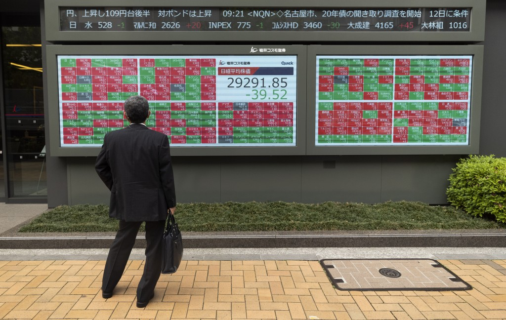 A man looks at an electric board showing Japan's Nikkei 225 index at a securities firm in Tokyo on Friday, May 7, 2021. Asian shares rose Friday on op...
