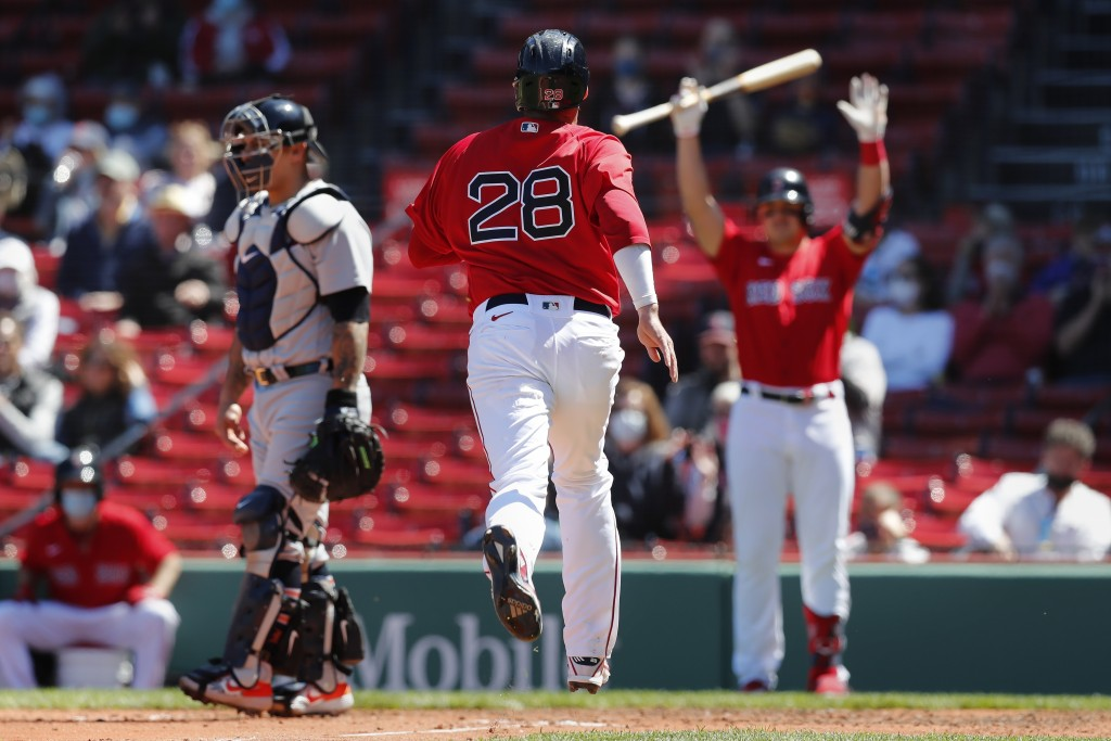 Boston Red Sox's J.D. Martinez (28) scores on a single by Rafael Devers during the third inning of a baseball game against the Detroit Tigers, Thursda...