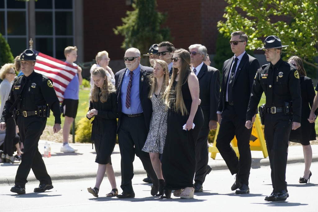 Family members escorted by law enforcement officers lead a processional to the Holmes Convocational Center for the funeral services of Watauga County ...
