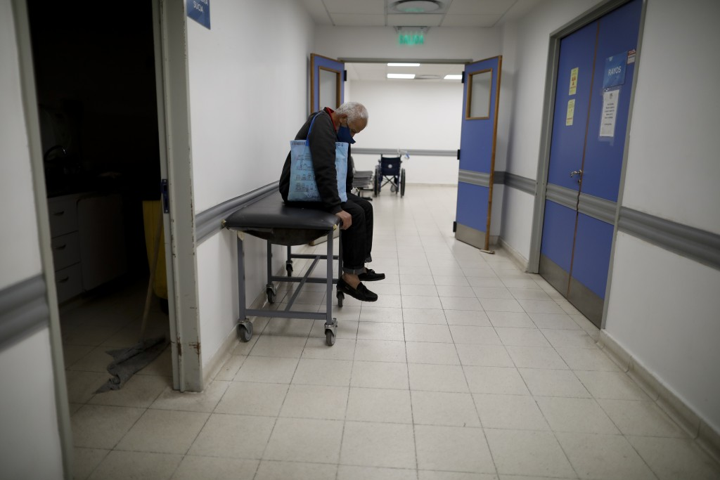 A man sits in a corridor as he waits for news of his wife who is suspected of having COVID-19 at the Dr. Norberto Raul Piacentini Hospital in Lomas de...