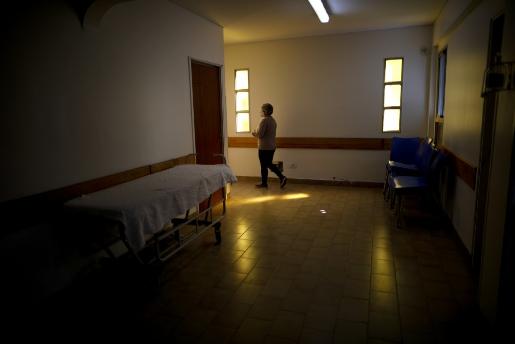 San Andres Clinic worker Alejandra Beccaria walks inside the clinic which has been occupied by its former workers since it closed at the start of the ...