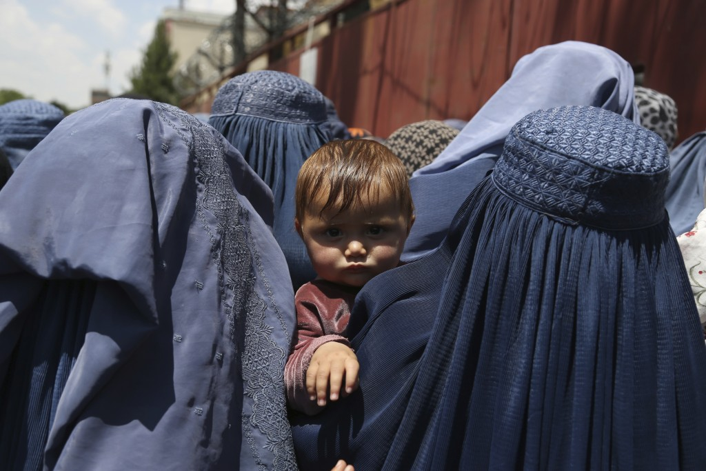 FILE - In this June 3, 2019 file photo, Afghan women wait to receive free food donated by Muslim Hands, a not-for-profit organization, in Kabul, Afgha...