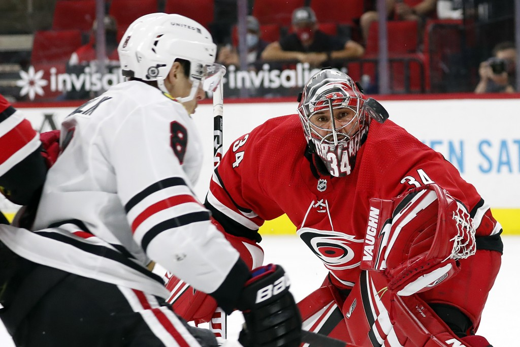 Carolina Hurricanes goaltender Petr Mrazek (34) tries to snare the puck in front of a charging Chicago Blackhawks' Dominik Kubalik (8) during the firs...