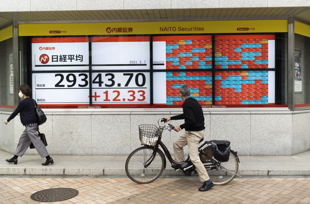 A man looks at monitors showing Japan's Nikkei 225 index at a securities firm in Tokyo on Friday, May 7, 2021. Asian shares rose Friday on optimism ab...