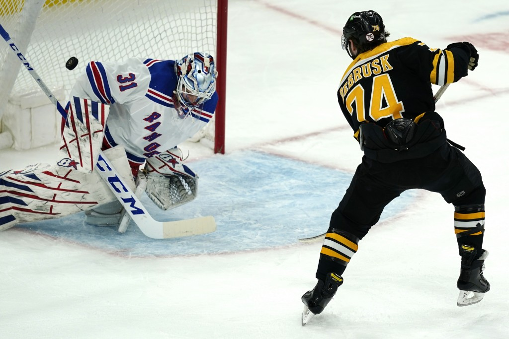 Boston Bruins left wing Jake DeBrusk (74) scores against New York Rangers goaltender Igor Shesterkin (31) on a breakaway in the second period of an NH...
