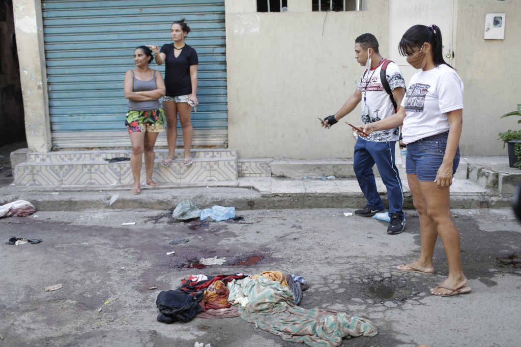 Residents take pictures of blood on the street after a police operation targeting drug traffickers in the Jacarezinho favela of Rio de Janeiro, Brazil...