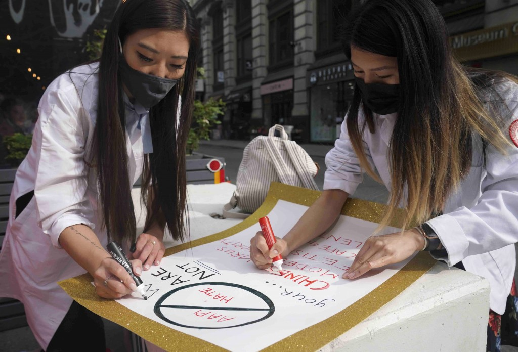 Dr. Michelle Lee, left, a radiology resident, and Ida Chen, right, a physician assistant student, prepare posters they carry at rallies protesting ant...