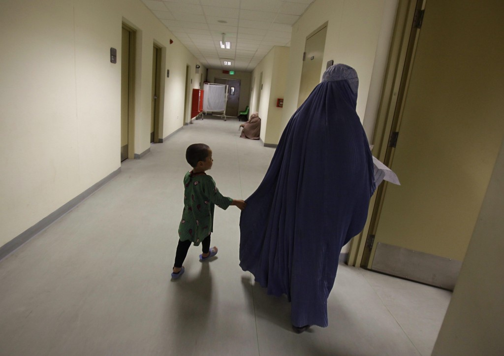 FILE - In this March 30, 2010 file photo, an Afghan woman walks the halls with her daughter searching for the right exam room at the Kandahar Regional...