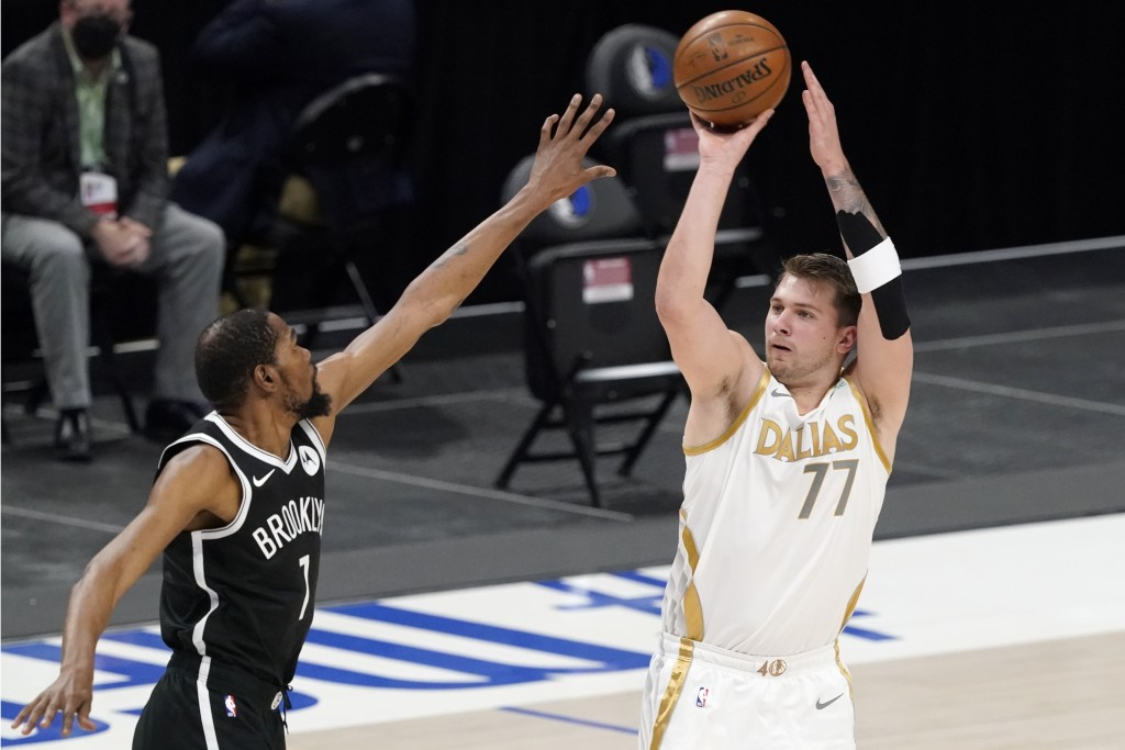 Brooklyn Nets forward Kevin Durant, left, defends as Dallas Mavericks guard Luka Doncic (77) shoots in the first half of an NBA basketball game in Dal...