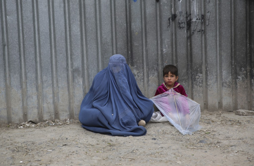 FILE - In this May 2, 2020 file photo, a woman waits to receive alms with her daughter during the Muslim fasting month of Ramadan, in Kabul, Afghanist...